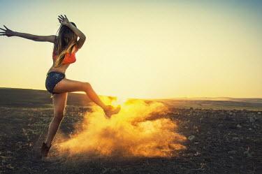 Metin Demiralay WOMAN KICKING UP DUST AT SUNRISE Women