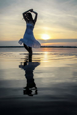 Stephen Carroll WOMAN DANCING IN WATER AT SUNSET Women