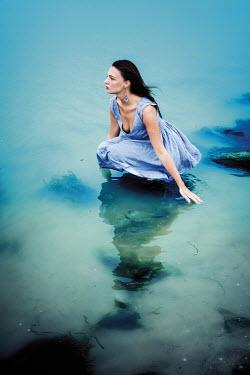 Ayal Ardon DARK HAIRED WOMAN KNEELING IN SEA WATER Women