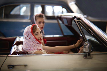 Ildiko Neer TWO RETRO WOMEN SITTING IN OPEN TOP CAR Groups/Crowds