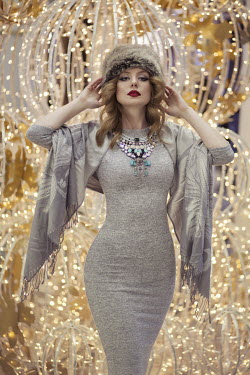 Maja Topcagic WOMAN WEARING FURRY HAT BESIDE FAIRY LIGHTS Women