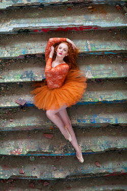 Rebecca Knowles BALLERINA WEARING ORANGE LYING ON STEPS Women