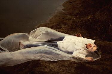 Marko Nadj MAN LYING ON SHORE UNDER SHEET Men