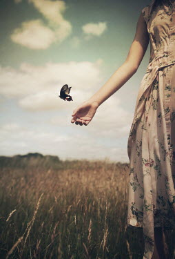 Mark Owen WOMAN RELEASING BUTTERFLY IN COUNTRYSIDE Women