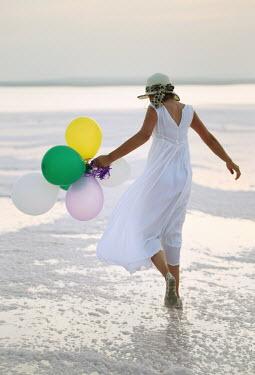 Nilufer Barin WOMAN WITH BALLOONS WALKING ON BEACH Women
