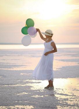 Nilufer Barin WOMAN ON SUNSET BEACH WITH BALLOONS Women