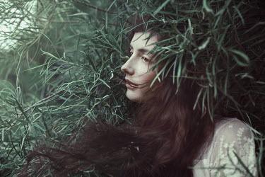 Marta Bevacqua DARK HAIRED WOMAN AMONG LEAVES OUTSIDE Women