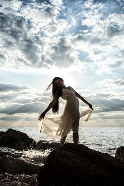 Nic Skerten WOMAN STANDING ON ROCKS BESIDE SEA AT DUSK Women