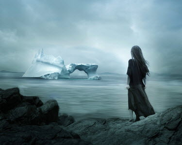 Patty Maher WOMAN ON ROCKS LOOKING AT ICEBERG IN SEA Women