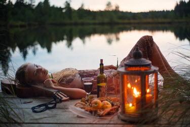 Christian Weiss WOMAN LYING ON GUITAR WITH WINE BESIDE LAKE Women