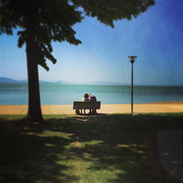 Marta Nardini COUPLE SITTING ON BENCH BESIDE SEA Couples