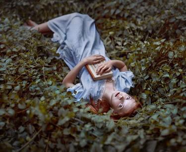 Irina Dzhul WOMAN WITH BOOK LYING AMONG LEAVES Women