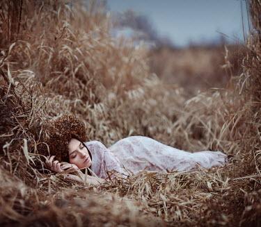 Irina Dzhul WOMAN ASLEEP IN OVERGROWN DRY GRASS Women
