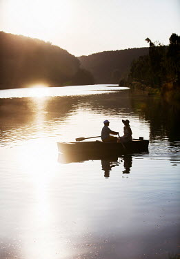 Nikaa COUPLE IN ROW BOAT ON SUNSET LAKE Couples