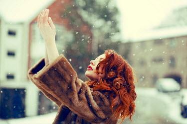 Rekha Garton WOMAN WEARING FUR COAT IN SNOWY CITY Women