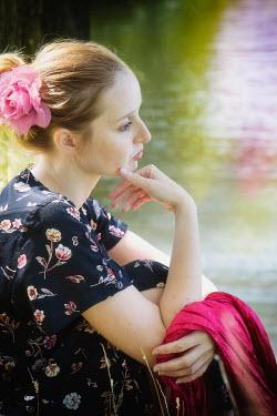 Yolande de Kort WOMAN IN FLORAL DRESS SITTING BESIDE LAKE Women