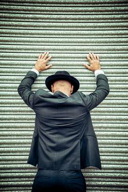 Nic Skerten MAN IN HAT FROM BEHIND TOUCHING METAL DOOR Men