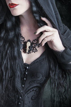 Victoria Davies WITCH WOMAN WEARING SKULL NECKLACE INDOORS Women
