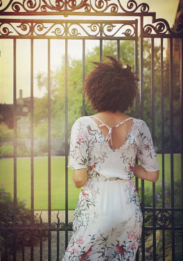 Mark Owen WOMAN LOOKING THROUGH GATE AT COUNTRY HOUSE Women