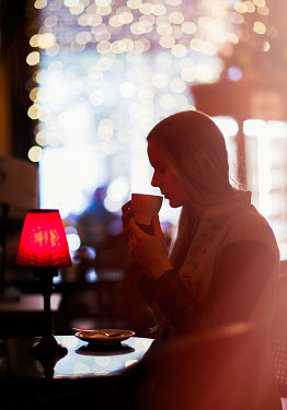 Nikaa WOMAN HOLDING CUP IN COFFEE SHOP Women