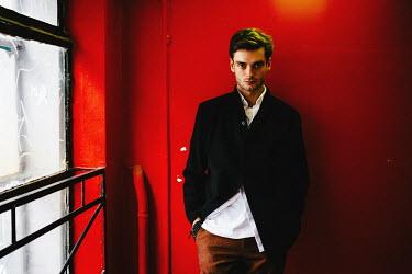 Daniil Kontorovich YOUNG MAN STANDING BY RED WALL INDOORS Men