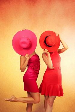 ILINA SIMEONOVA TWO WOMEN HOLDING COLOURFUL HATS INDOORS Groups/Crowds