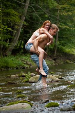 Joshua Sheldon MAN CARRYING HAPPY WOMAN OVER STREAM Couples