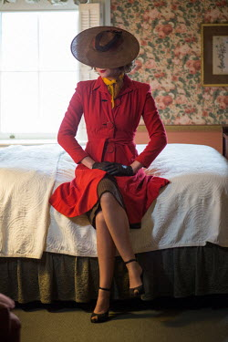Elisabeth Ansley VINTAGE WOMAN IN HAT SITTING ON BED Women