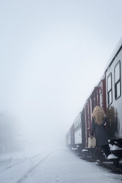 Carmen Spitznagel WOMAN CLIMBING INTO TRAIN IN SNOWY WEATHER Women