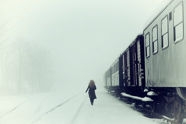 Carmen Spitznagel WOMAN WALKING BY TRAIN IN SNOWY WEATHER Women