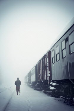 Carmen Spitznagel MAN WALKING BY TRAIN IN SNOWY WEATHER Men