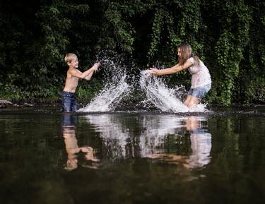 Stephen Carroll TWO CHILDREN SPLASHING WATER IN LAKE Children