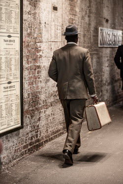 Colin Hutton MAN WALKING WITH SUITCASE TO TRAIN STATION Men