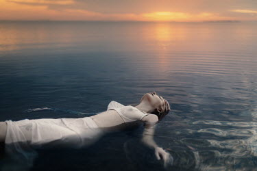 Tatiana Mertsalova WOMAN FLOATING IN OCEAN AT SUNSET Women