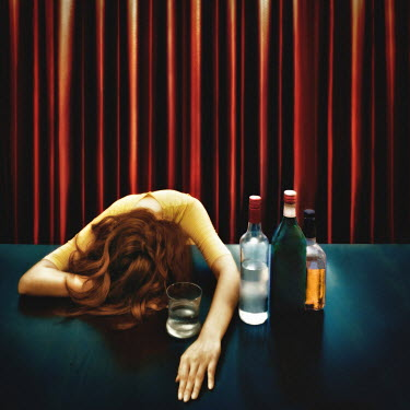 Vanessa Ho WOMAN WITH HEAD ON TABLE NEAR ALCOHOL Women