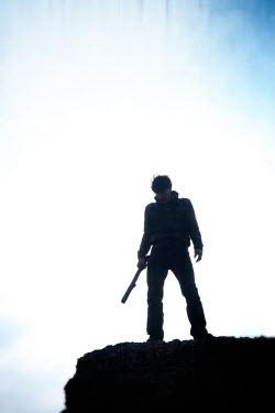 Tim Robinson MAN STANDING ON CLIFF WITH BAT Men