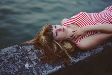 Anna Rakhvalova RED HAIRED WOMAN LYING ON WALL BY WATER Women