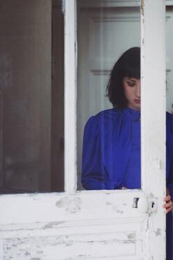Anna Rakhvalova DARK HAIRED WOMAN STANDING BEHIND DOOR Women
