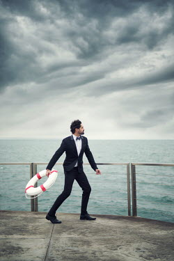 Paulo Dias MAN IN SUIT THROWING LIFE BUOY IN SEA Men