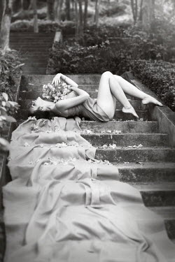 Irina Brana WOMAN LYING ON STEPS OUTSIDE Women