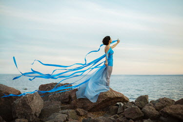 Irina Brana WOMAN BESIDE OCEAN WITH STREAMERS Women