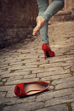 Emma Goulder WOMAN DROPPING STILETTO SHOE ON STREET Women