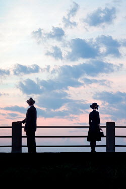Susan Fox SILHOUETTE OF COUPLE STANDING APART ON PIER Couples