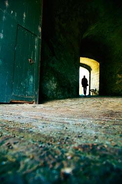 Yolande de Kort SILHOUETTE OF MAN IN DERELICT DOORWAY Men