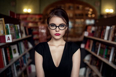 Maxim Guselnikov YOUNG WOMAN WEARING GLASSES IN LIBRARY Women