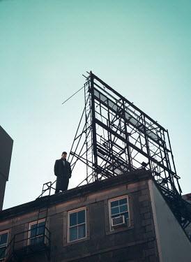 Mark Owen MAN STANDING ON ROOF OF BUILDING Men