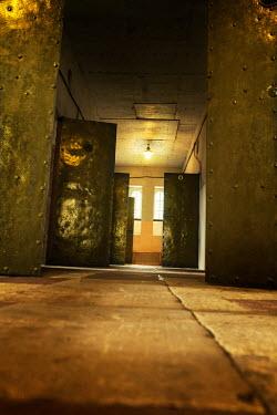 Stephen Mulcahey Prison cell doors left open in corridor Interiors/Rooms