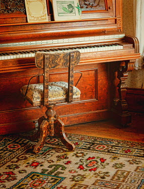 Jill Battaglia vintage piano and stool on patterned rug Musical Instruments