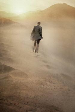 Nik Keevil MAN IN SUIT WALKING ON SAND DUNE Men