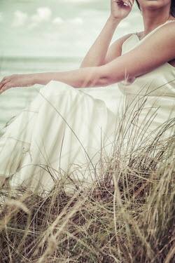 Nic Skerten WOMAN IN WHITE DRESS SITTING BY SEA Women